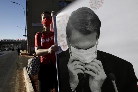 지난 8월 브라질 브라질리아에서 한 시위자가 보우소나로 브라질 대통령이 마스크 착용법을 몰라 헤매는 사진을 들고 있다. 시위대는 보우소나루 대통령의 소극적인 대응으로 브라질 내 코로나19 피해가 늘었다며 책임을 묻고 있다. [AP=연합뉴스]