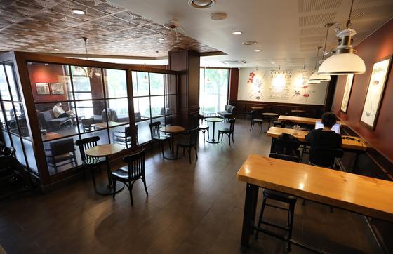 사회적 거리두기 조치가 '2단계'로 하향 조정된 14일 오전 서울 송파구의 한 카페전문점에서 시민들이 커피를 마시고 있다. [뉴시스]