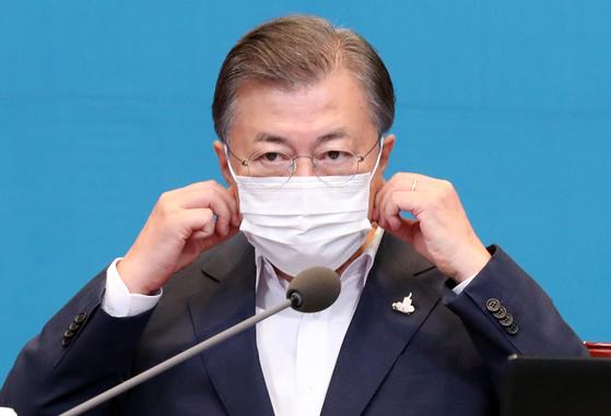 문재인 대통령이 14일 오후 청와대 여민관에서 열린 수석보좌관회의에 참석해 머리발언을 하기 앞서 마스크를 벗고 있다. 청와대사진기자단