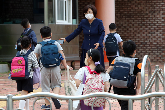 광주 광산구 선암동 한 초등학교에서 교장 선생님이 학생을 맞이하고 있다. 연합뉴스