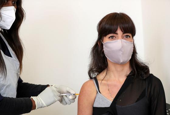 남아프리카 공화국 요하네스버그에서 코로나19 백신 임상 시험에 자원한 로빈 포르테우스가 접종을 받고 있다. 백신 개발은 이런 자원자들의 용기와 헌신에 힘입어 착착 진행 중이다. 임상 시험 자원자도 코로나 영웅으로 부르기에 모자람이 없다. 이처럼 백신 임상 시험이 전 세계에서 진행되고는 있지만 11월 3일 열리는 미국 대선 전에 공급이 이뤄질지는 갈수록 불투명해지고 있다. 로이터=연합뉴스