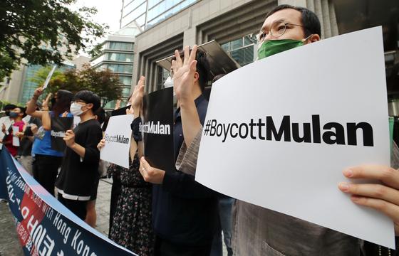 지난 7월 1일 오후 서울 강남 월트디즈니코리아 본사가 있는 건물 앞에서 열린 영화 '뮬란' 보이콧 선언 기자회견에서 참석자들이 피켓을 들고 있다. [연합뉴스]