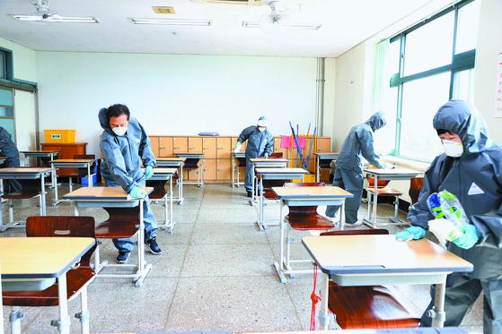 코로나19 확진자가 발생한 서울공업고등학교에서 15일 오전 동작구 4개 동 방역지원단이 책상 등 교실에 대해 긴급방역을 하고 있다. [뉴스1]