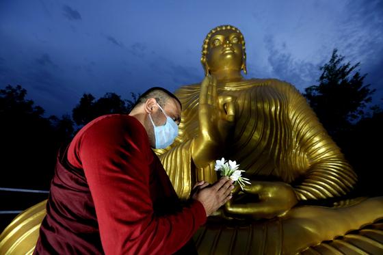 카스트 제도에서 고통받은 불가촉천민들이 최근 힌두교에서 불교로 개종하는 사례가 늘고 있다. 인도 보팔에서 불교 승려가 마스크를 쓴 채 부처님 상 앞에 꽃을 들고 기도를 올리고 있다. [EPA=연합뉴스]