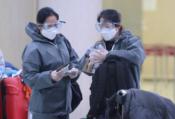지난 3월 10일 제주국제공항 출국장에서 중국인들이 코로나19 예방을 위해 고글과 우비, 마스크 등을 착용하고 순서를 기다리고 있다. [뉴스1]