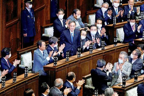 일본 집권 자민당 스가 요시히데 총재가 16일 도쿄 중의원에서 새 총리로 선출된 직후 의원들의 박수를 받으며 자리에서 일어서 있다. 이날 표결에 참여한 자민당의 다카토리 슈이치의원이 18일 코로나19 양성 판정을 받았다. 로이터=연합뉴스