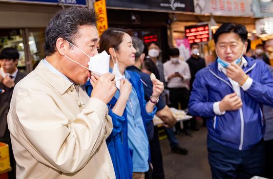 이낙연 더불어민주당 대표가 18일 오후 서울 종로구 통인시장을 방문해 마스크 아래로 구입한 떡을 맛보고 있다. [뉴스1]