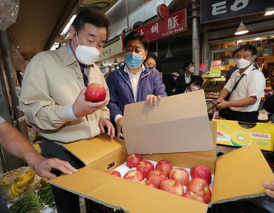 이낙연 더불어민주당 대표가 18일 오후 서울 종로구 통인시장을 방문해 백년당원에게 보낼 사과를 살펴보고 있다. 뉴스1