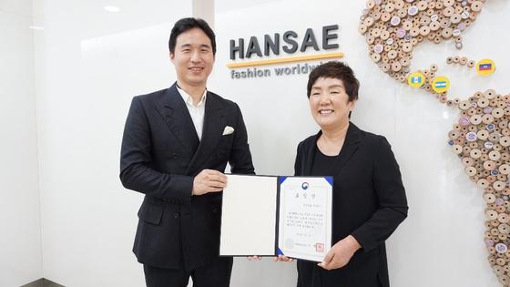 김익환(왼쪽) 한세실업 부회장과 조희선 대표가 여성가족부 장관 표창장을 들고 밝게 웃고 있다.