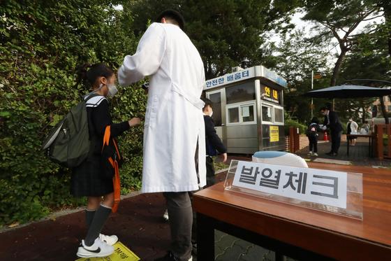 수도권 지역 유·초·중·고 학생들의 등교가 한달여만에 재개된 21일 오전 서울 노원구 화랑초등학교 학생들이 등교하며 발열 체크를 하고 있다. 연합뉴스