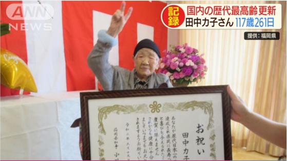 지난 19일 일본 최고령 다나카 가네 할머니가 후쿠오카현 지사로부터 축하장을 받은 뒤 손으로 브이를 하고 있다. [TV아사히 캡쳐]