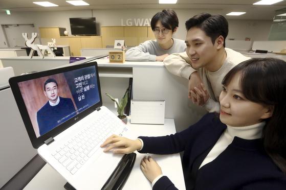 올 1월 서울 여의도 LG트윈타워에서 직원들이 구광모 LG 대표의 디지털 신년 영상 메시지를 노트북으로 시청하고 있다. [사진 LG]