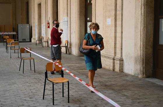 지난 20일(현지시간) 이탈리아 로마 시내에서 마스크를 쓴 여성이 투표에 참여하고 있다. 신종 코로나바이러스 감염증(코로나19) 사태 속 치러진 이번 개헌안 투표는 53.8%의 투표율을 기록했다. [AFP=연합뉴스]