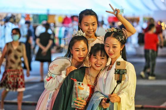 지난 8월 27일 중국 후베이성 우한에서 시민들이 스마트폰으로 사진을 찍고 있다. 마스크는 쓰지 않았다.[AFP=연합뉴스]