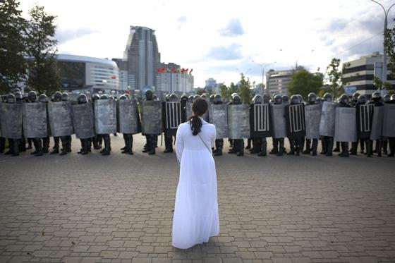 지난 13일 벨라루스 민스크에서 열린 대선 불복 시위 현장에 참석한 한 여성 시위자가 흰 옷을 입은 채 경찰들 앞에 서있다. [AP=연합뉴스]