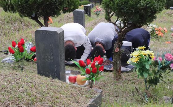 지난 13일 코로나19 여파로 이른 성묘에 나선 시민이 부산 금정구 영락공원에서 벌초를 한 뒤 조상 묘에 절을 하고있다. 송봉근 기자
