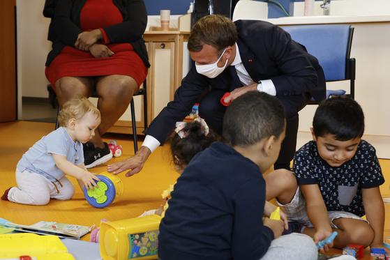 에마뉘엘 마크롱 프랑스 대통령이 23일(현지시간) 파리에서 한 아이와 놀아주고 있다. 마크롱 대통령은 이날 프랑스의 '배우자 출산휴가'를 기존 14일에서 28일로 연장하겠다고 밝혔다. [연합뉴스]