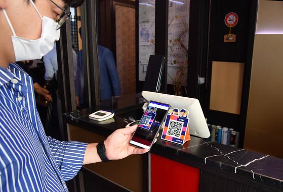 18일 서울 중구 한 음식점에서 서울시 관계자들이 제로페이 QR 코드를 활용한 전자출입명부 관리 시연을 하고 있다. 연합뉴스