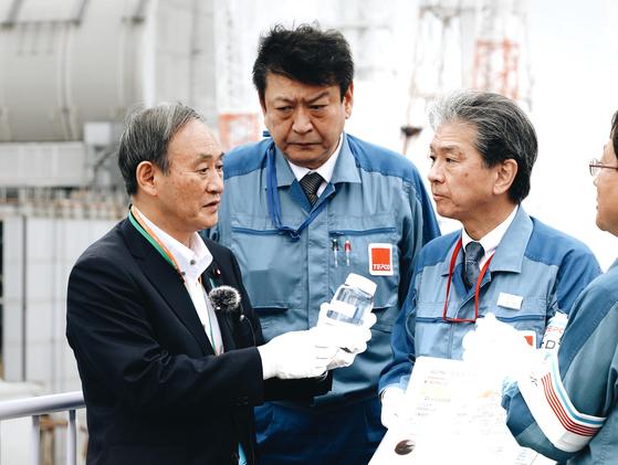 """스가 요시히데(왼쪽) 일본 총리가 지난 26일 취임 후 처음으로 후쿠시마 제1원전을 방문해 도쿄전력 관계자의 설명을 듣고 있다. 스가 총리가 들고 있는 병 안에는 원전에서 발생한 오염수를 한 차례 정화한 물이 담겨있다. 스가 총리는 오염수 처리와 관련 """"되도록 빨리 정부가 책임을 지고 처분 방법을 결정하겠다""""고 말했다. [스가 총리 인스타그램]"""