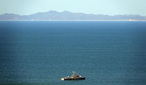 25일 황해도 등산곶 해안이 보이는 우리 영해에서 해군 함정이 경비하고 있다. 정면에 보이는 해안이 등산곶 인근 해안이다. 해양수산부 공무원 이모(47)씨는 등산곶 해안에서 북한군에 살해돼 시신이 불태워졌다. [연합]