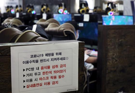 고위험시설로 일시 지정됐던 PC방의 운영이 재개된 지난 14일 서울 성동구의 한 PC방에 음식물 섭취 금지, 띄어 앉기 등이 적시된 예방 수칙 안내문이 붙어 있다. 뉴시스