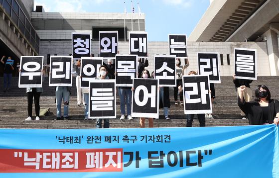 모두를위한낙태죄폐지공동행동 관계자들이 28일 서울 종로구 세종문화회관 앞에서 열린 '낙태죄' 완전 폐지 촉구 기자회견에서 퍼포먼스를 하고 있다. 연합뉴스