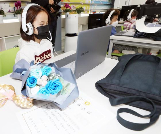 지난 4월, 청주시 상당구 낭성초등학교 '온라인 입학식'에서 신입생이 헤드셋을 착용하고 컴퓨터를 바라보고 있다. 연합뉴스