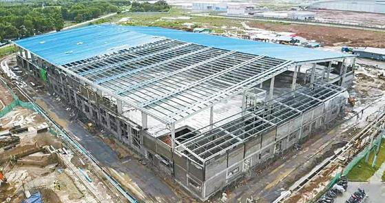 한세실업은 미얀마에 추가 생 산시설을 건설하고 있다. 독자 개발한 스마트팩토리 시스템 '햄스'도 갖춘다. 사진은 미얀 마 공장동(위, 지난 6월 촬영)과 완공 조감도. [사진 한세실업]