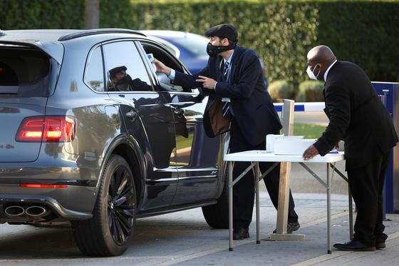 토트넘 훈련장 진입 차량을 대상으로 탑승자 체온 검사를 진행하는 보안요원들. [로이터=연합뉴스]