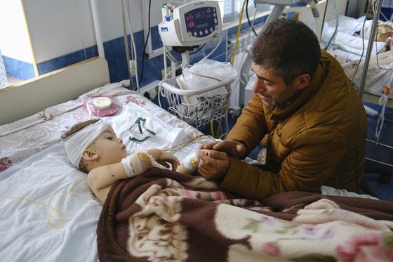 아르메니아-아제르바이잔 분쟁 지역인 나고르노-카라바흐의 한 병원에서 28일(현지시간) 한 아빠가 폭격으로 다친 아들을 돌보고 있다. AP통신=연합뉴스
