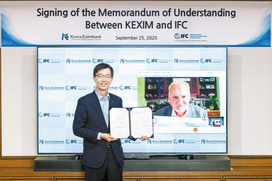 방문규 수출입은행장(사진 왼쪽)과 필립 르 우에루 IFC 사장이 지난 25일 화상 서명식을 통해 업무 협약서에 서명했다.  [사진 한국수출입은행]