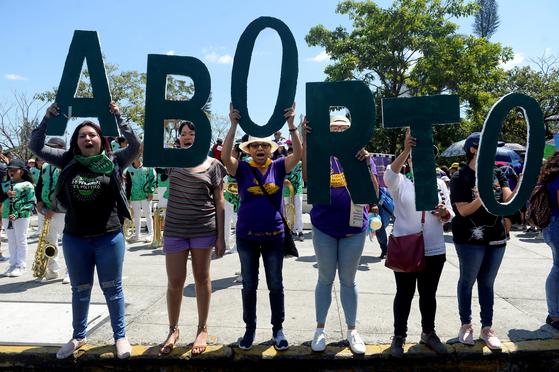 엘살바도르의 여성들이 올해 3월 '세계 여성의 날'을 맞아 '낙태'라고 쓰인 영어 단어 피켓을 들어보이고 있다. [로이터=연합뉴스]