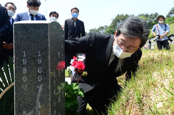 지난 5월 17일, 광주 국립 5·18민주묘지를 찾은 유승민 전 미래통합당 의원이 한 희생자의 묘비를 어루만지고 있다. 뉴스1