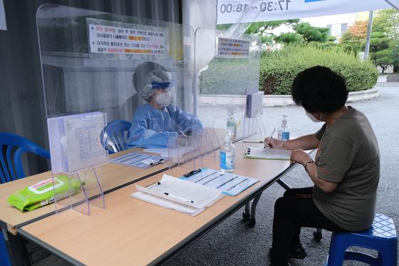 추석을 하루 앞둔 30일 오전 광주 광산구보건소 선별진료소에서 한 의료진이 코로나19 피검사자에게 사전문진표 작성법을 안내하고 있다. 뉴스1