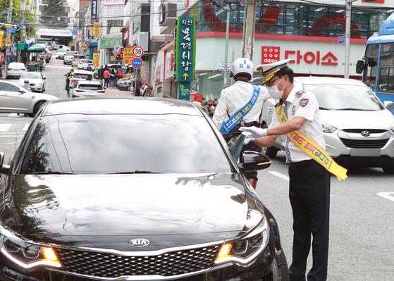 24일 대구 수성구 지산동 목련시장네거리에서 대구경찰청 경찰관들이 보행자 보호 의무를 잘 지킨 운전자에게 감사 선물을 전하는 행사를 진행하고 있다. 대구경찰청