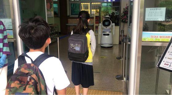 지난 7월 서울 서초구 우암초 4학년 학생이 인공지능(AI) 로봇 앞에서 체온 검사를 받고 있다. 중앙포토
