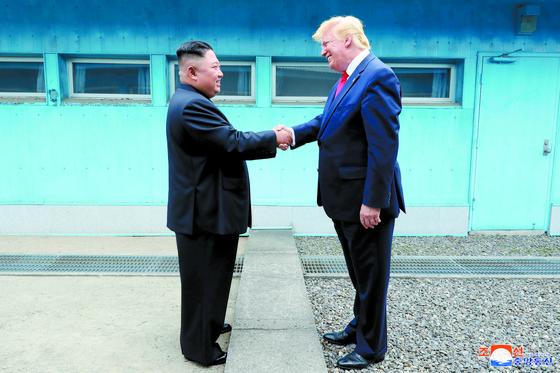 도널드 트럼프 미국 대통령과 북한 김정은 국무위원장이 판문점에서 군사분계선을 사이에 두고 악수하고 있다.조선중앙통신