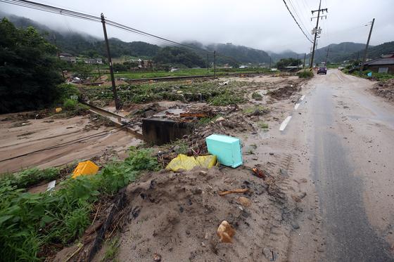 지난 8월 충북 충주시 산척면의 한 마을 진입로에 수해로 떠내려온 부유물 등이 방치돼 있다. [연합뉴스]