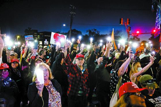 트럼프 미국 대통령이 코로나19 확진 판정을 받고 입원한 메릴랜드주 월터리드 군병원 앞에서 3일(현지시간) 지지자들이 휴대전화 조명을 밝히고 쾌유를 기원하고 있다. [EPA=연합뉴스]