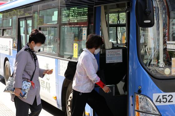 5일 서울 강남구 강남역 인근에서 시민들이 마스크를 쓰고 버스에 탑승하고 있다. 뉴시스