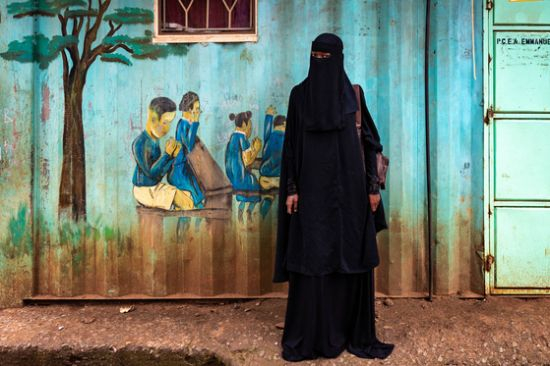 기도하는 어린이들의 모습이 담긴 벽화와 검은 천의 무슬림 전통의상 '차도르'를 입고 그 앞에 선 한 소녀의 모습. 배경과 피사체가 주는 상반된 느낌이 사진의 메시지를 더욱 강조하고 있다. [사진 허호]