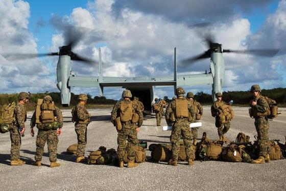 미국 해병대가 수직이착륙 수송기인 MV-22 오스프리에 타기 위해 대기하고 있다. [미 해병대]