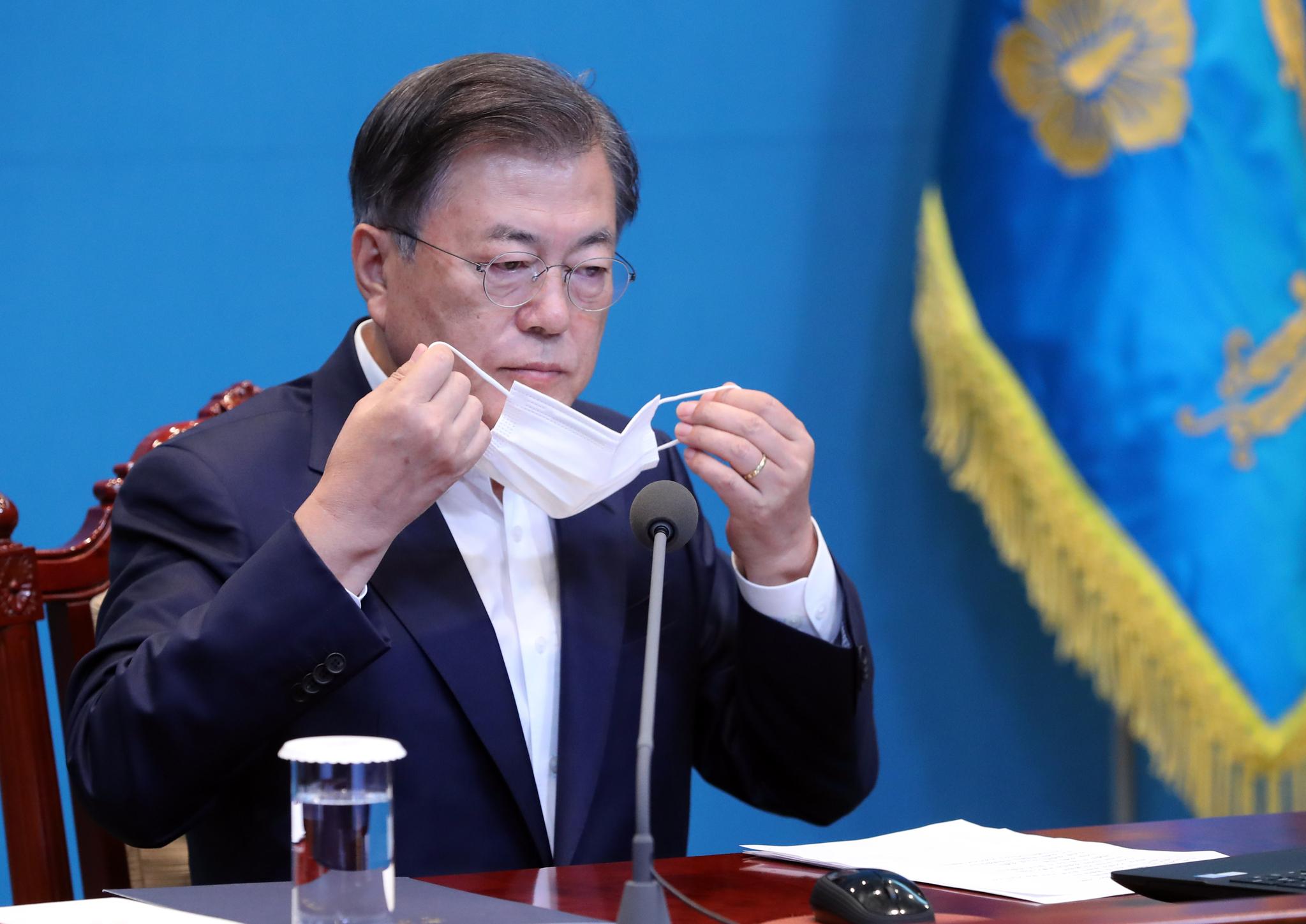 문재인 대통령이 5일 청와대에서 열린 수석·보좌관 회의에서 발언을 마친 뒤 마스크를 쓰고 있다. 연합뉴스