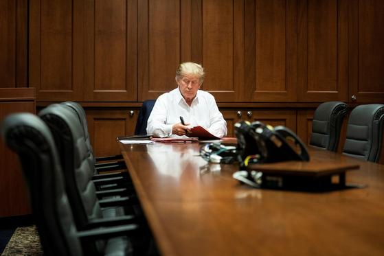 """코로나19로 입원치료 중인 도널드 트럼프 미국 대통령이 3일(현지시간) 메릴랜드주 베세즈다의 월터리드 군 병원 콘퍼런스룸에서 업무를 보고 있다. 그는 이날 트위터에 올린 4분짜리 영상 메시지에서 '이곳에 올 때는 몸이 안 좋다고 느꼈으나 지금은 좋아졌다""""고 밝혔다. 트럼프 대통령의 코로나19 확진은 한 달도 남지 않은 미국 대선 판세를 뒤바꿀 수 있는 변수가 될 전망이다. [AP=연합뉴스]"""