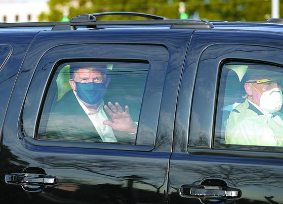 트럼프 대통령이 4일 메릴랜드 월터 리드 메디컬센터를 잠시 나와 차안에서 지지자들에게 손을 흔들고 있다. AFP=연합뉴스