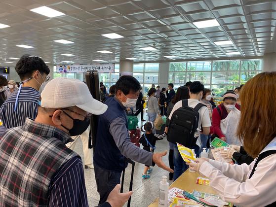 지난달 28일 제주공항을 통해 들어온 입도객들이 도가 지원하는 마스크를 받고 있다. 최충일 기자