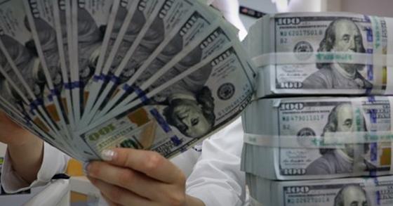 서울 명동 하나은행 위폐감별실에서 직원이 미국 달러를 살펴보고 있다. 연합뉴스