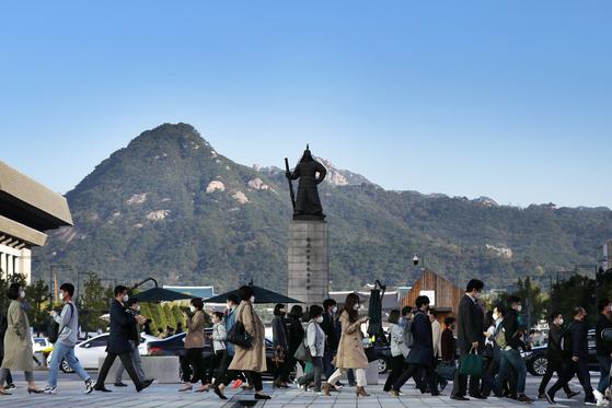 지난 7일 오전 서울 종로구 광화문 네거리에서 쌀쌀해진 날씨에 겉옷을 챙겨입은 시민들이 출근길 발걸음을 재촉하고 있다. 뉴스1
