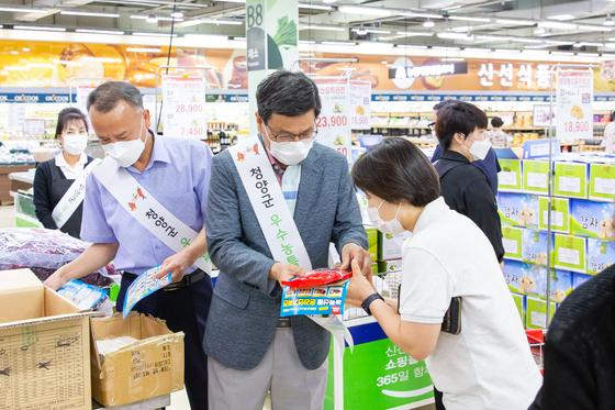 지난달 18일 대전 유성에 개장한 청양 먹거리 직매장에서 김돈곤 청양군수(가운데)가 매장을 찾은 손님에게 물건을 소개하고 있다. [사진 청양군]
