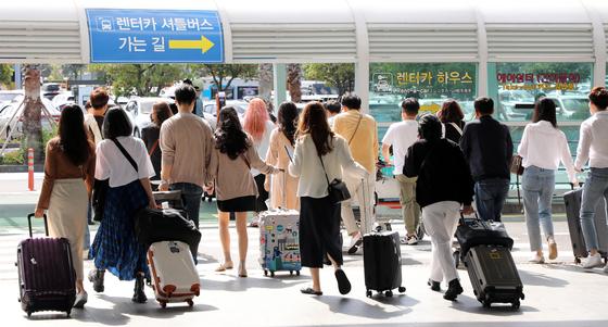추석 전 마지막 주말인 27일 제주국제공항에 도착한 관광객들이 횡단보도를 건너며 렌터카 하우스로 향하고 있다. 뉴스1